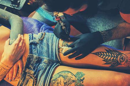 Close up image of the bearded tattoo male artist makes a tattoo on a female leg.