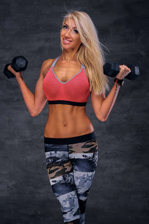 Sexy blond female fitness model dressed in a pink sportswear holds dumbbells.