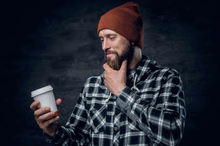 lumberjack shirt: A brutal bearded male dressed in a hat and fleece shirt, drinks coffee from a paper glass.