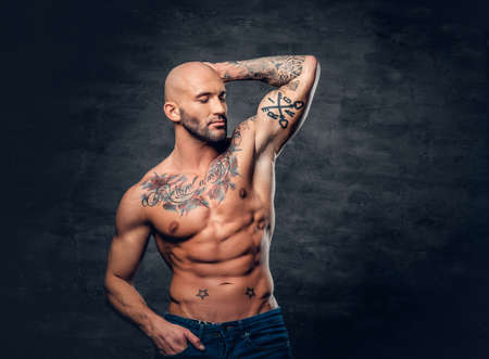 suntanned: Studio portrait of shirtless shaved head, muscular male with tattoos on torso touch his head.