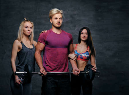 suntanned: Threesome fitness model of blond and brunette slim women and a man holds barbell posing over grey background.