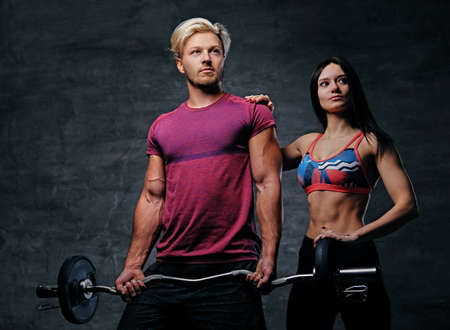 suntanned: The athletic, blond male holds barbell weight and slim fitness female model over dark grey background. Stock Photo