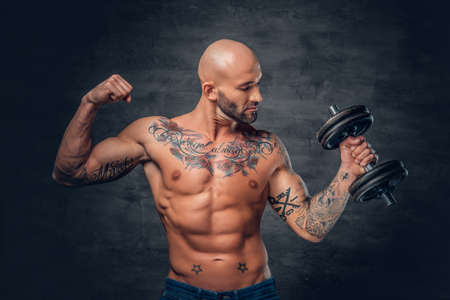 suntanned: Studio portrait of shaved head sporty male with tattoos on his chest and arms holds dumbbell.