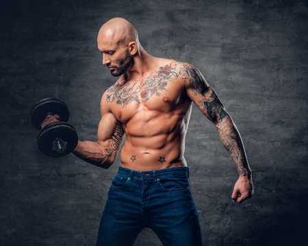 suntanned: Positive shaved head shirtless male dressed in a jeans holds the dumbbell over dark grey background.