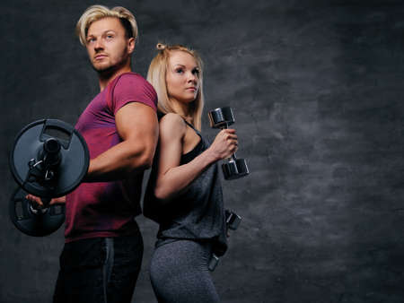 suntanned: An attractive fitness couple of sporty male holds barbell and slim blond female holds dumbbells over grey background