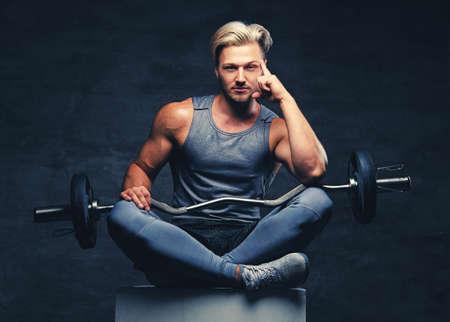 Een blond, atletisch mannetje gekleed in een grijze sportkleding zit op een witte houten doos en houdt barbeel. Stockfoto
