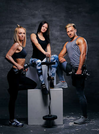 suntanned: Studio image of full body sporty blond and brunette women and an athletic man posing on a white box over grey background. Stock Photo