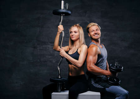 suntanned: Studio portrait of attractive fitness couple holds barbell and dumbbells, sit on a wooden box over dark grey background. Stock Photo