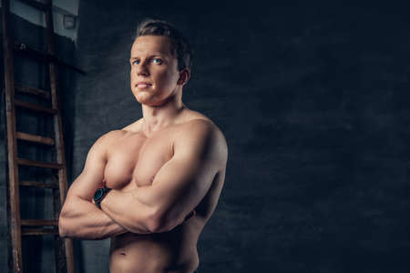 suntanned: Studio portrait of shirtless athletic suntanned male with crossed arms.