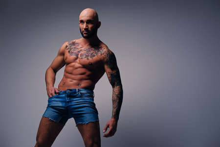 suntanned: Studio portrait of shirtless shaved head, muscular male with tattoos on his torso dressed in a denim shorts over grey vignette background.