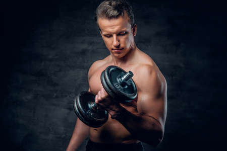 suntanned: Shirtless athletic male doing biceps exercise with dumbbells.
