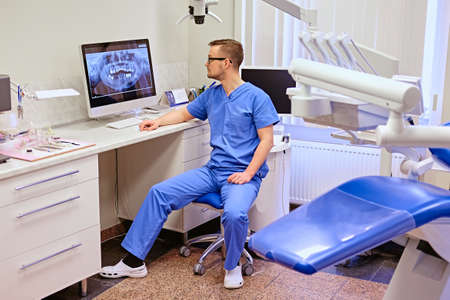 rentgen: Male dentist looking at teeth x-ray on the computer in a dentist office. Stock Photo