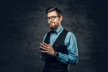 An elegant bearded hipster male dressed in a blue shirt and waistcoat over grey vignette background.