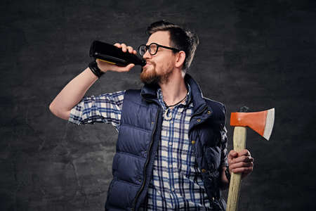 Portrait of funky bearded hipster male dressed in fleece shirt holds an axe and drinks craft bottled beer.