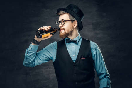 A bearded hipster male dressed in a blue shirt, elegant waistcoat and top hat drinks craft bottle beer.