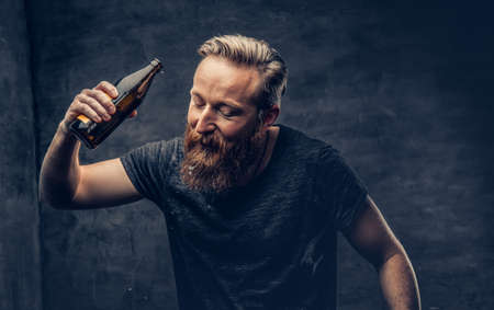 Emotional, funny redhead bearded drunk hipster male holds craft bottled beer.