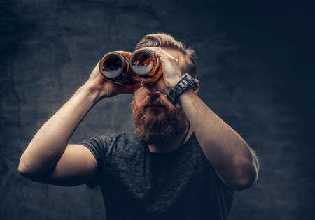 Funny redhead bearded male looking through two craft beer bottle like through binoculars. Foto de archivo