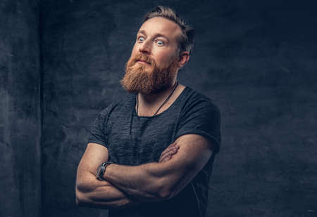 Studio portrait of redhead bearded hipster male with crossed arms over grey background.
