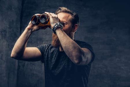 Zábavný rudovlasý vousatý muž hledí přes dvě lahvičky piva, jako je dalekohled.