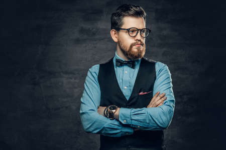 Successful bearded male with crossed arms, dressed in elegant shirt and waistcoat and eyeglasses.