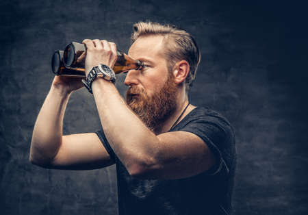 Funny redhead bearded male looking through two craft beer bottle like through binoculars. Reklamní fotografie