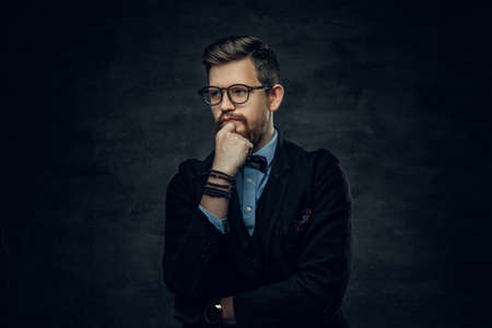 Handsome bearded elegant male in eyeglasses dressed in a dark blue suit with bow tie over grey vignette background.