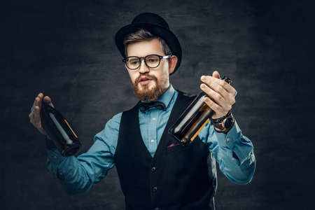 Portrait of bearded hipster male dressed in a blue shirt, elegant waistcoat and top hat holds two craft beer bottles with a think of a party.