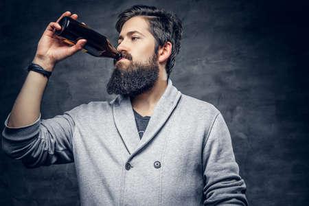 Portrait of bearded hipster male drinks craft bottled beer. Stock Photo