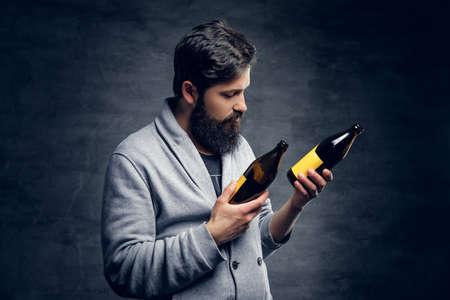 Full throttle bearded male holds two craft beer bottles.