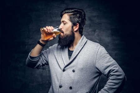 Portrait of bearded hipster male drinks craft bottled beer. Reklamní fotografie