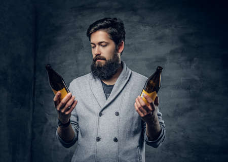 Full throttle bearded male holds two craft beer bottles and looking on its amber color. Reklamní fotografie