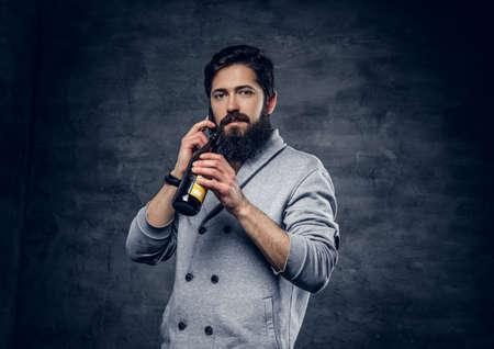Full throttle bearded male dressed in a grey wool jacket holds craft beer bottle.