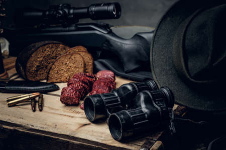 Retro hunting ammunition of rifle and binoculars. Delicious sausage and brown bread on a wooden table. Stock Photo
