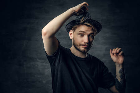 A positive hipster male dressed in a black t shirt and tweed hat.