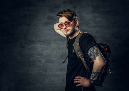 Portrait of a handsome tattooed traveler male with backpack dressed in a black t shirt and red sunglasses. Reklamní fotografie