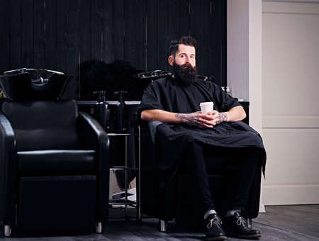Full throttle bearded hipster male drinks coffee before the hair styling in a hairdressers salon.