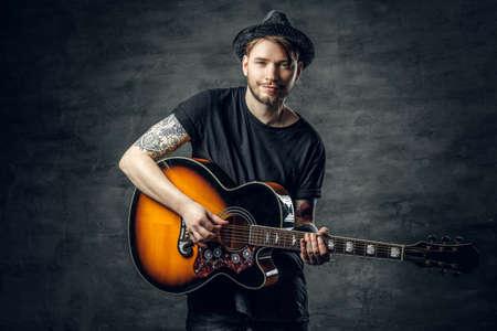Jonge modieuze hipster blues en jazz akoestische gitaarspeler met tatoeages op zijn armen die melodie spelen.