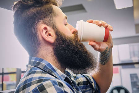 throttle: A stylish bearded hipster male dressed in a fleece shirt, drinks coffee in a hairdressers salon.