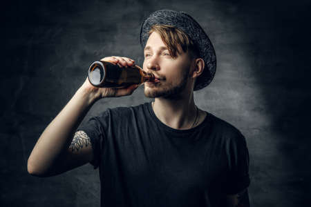 Bearded hipster male with tattoos on his arms, dressed in a black t shirt and top hat drinks craft bottled beer. Reklamní fotografie