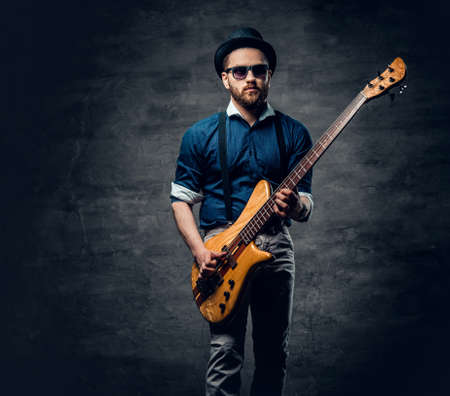 Studio portrait of the hipster bass player dressed in cylinder hat. 免版税图像