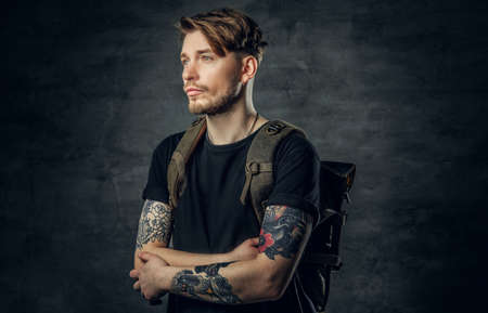 Portrait of a handsome tattooed traveler male with crossed arms and backpack on his back.