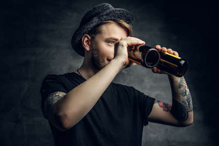 Bearded hipster male with tattoos on his arms, dressed in a black t shirt and top hat looking through two beer bottles.