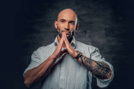 Praying shaved head male with tattoos on his arm.