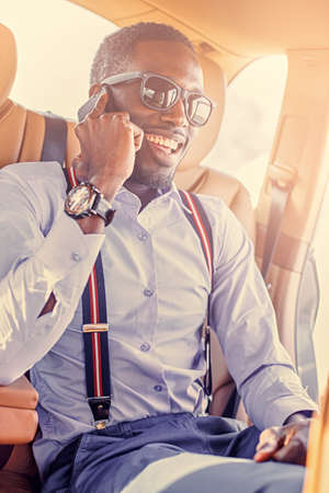 Elegant black American maleusing smartphone in a car. Filtered warm toned image.