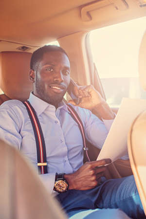 Elegant black American male read the paper document in a car. Filtered warm toned image.