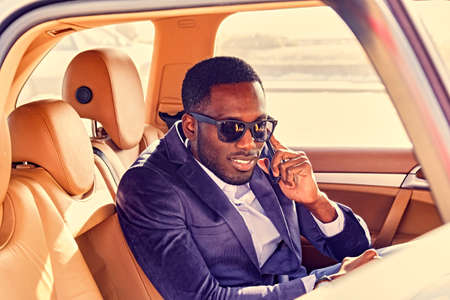 Portrait of black American elegant male talks on smartphone in a car. Filtered warm toned image.