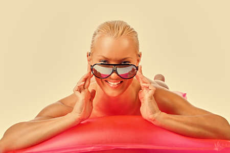 Portrait of a blond female in sunglasses lying on water mattress. Filtered pink toned image. photo