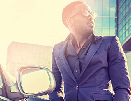 Casual black American male posing near the car. Filtered warm toned image.
