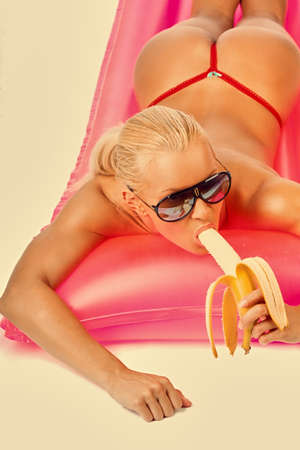 Portrait of a blond female in sunglasses lying on water mattress and eats banana. Filtered pink toned image. photo