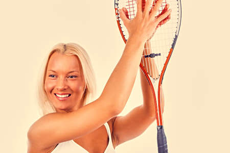 The blond sporty female holds tennis racket. Pink toned image. photo